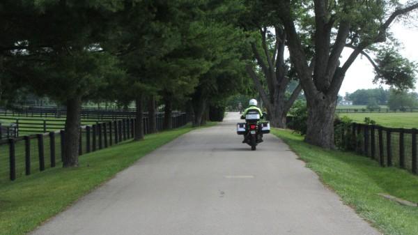 Jim Park rides along a narrow lane between horse farms